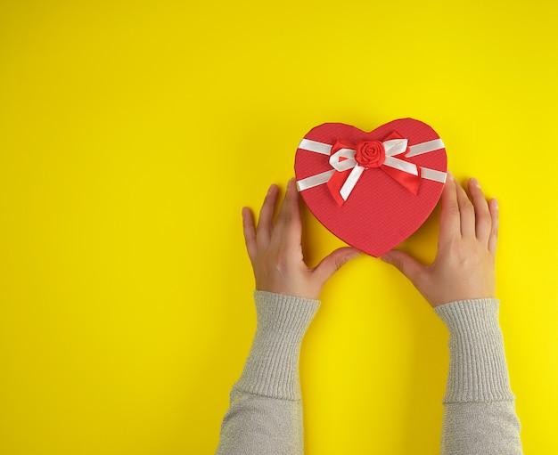 Handen houden een papieren gesloten rode doos in de vorm van een hart op een geel