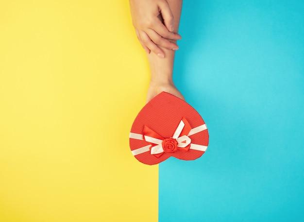 Handen houden een papieren gesloten rode doos in de vorm van een hart vast