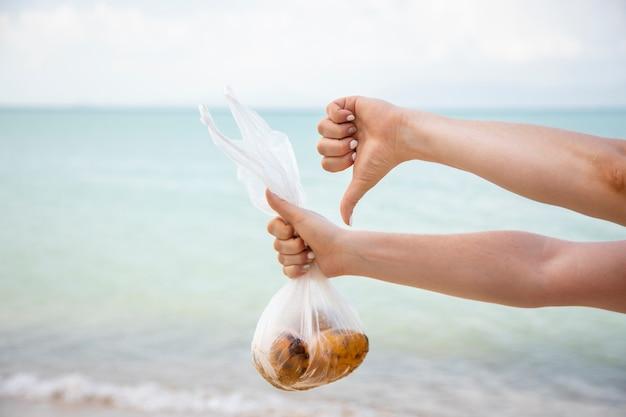Handen houden een plastic zak met fruit vast en tonen een duim naar beneden tegen de achtergrond van de zee. geen gezicht. het concept van vervuiling van de natuur en een bewuste houding ten opzichte van de ecologie van de planeet.