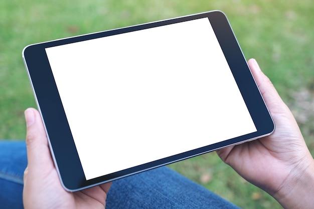 Handen houden en gebruiken van zwarte tablet-pc met leeg wit scherm horizontaal zittend in het park