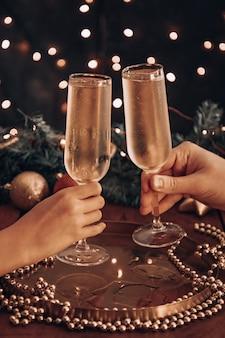 Handen houden glazen champagne vast en kijken tussen de kerstverlichting.