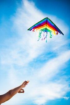 Handen houden mooie en heldere regenboogvlieger vast