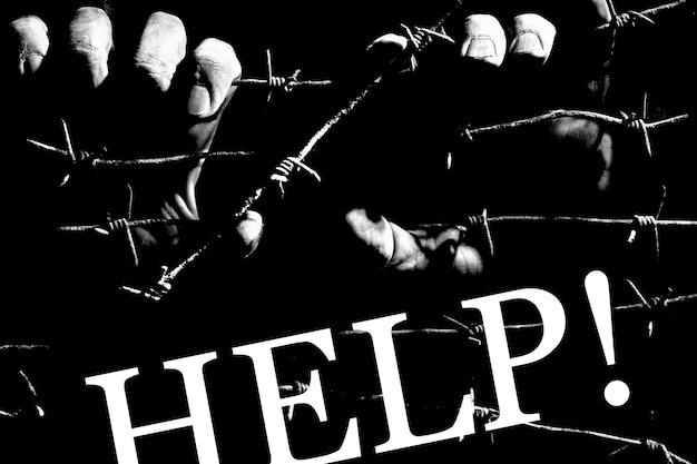 Handen houden prikkeldraad vast in het donker van de nacht verlicht door een gevangenislantaarn