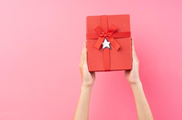 Handen houden rode geschenkdozen op een roze muur