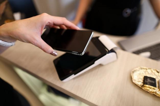 Handen houden smartphone voor contactloos betalen