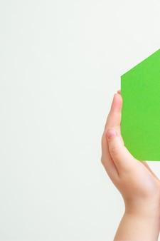 Handen houdt groen papier huis.