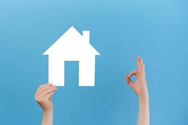 Handen houdt huismodel vast en maakt een goed gebaar