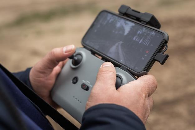 Handen in afstandsbediening om een drone van dichtbij te besturen