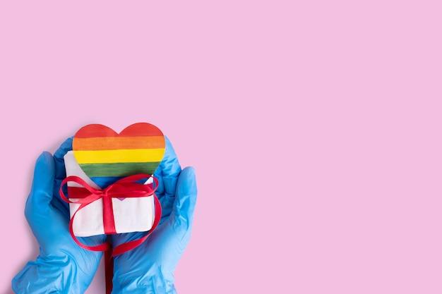 Handen in beschermende blauwe handschoenen houden een zelfgemaakt regenboogdocument hart en een geschenkdoos met een rood lint op een roze achtergrond, kopieer ruimte. veilig lgbtql-concept
