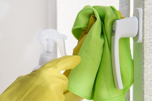 Handen in beschermende handschoenen met doek en spray maken de raamkruk schoon