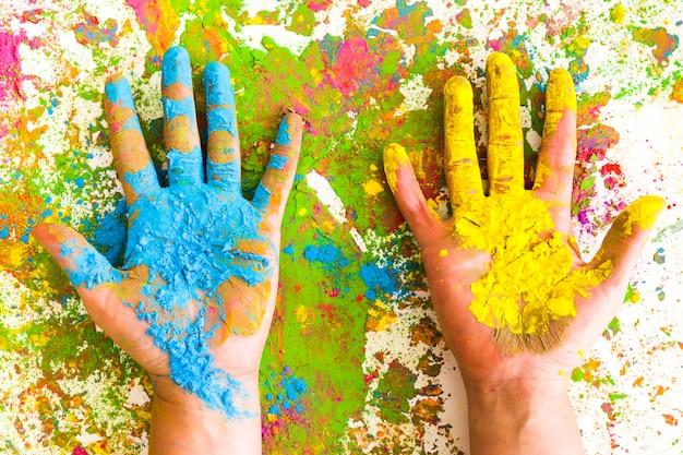 Handen in blauwe en gele kleuren op heldere, droge kleuren