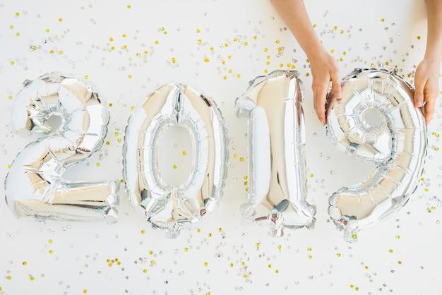 Handen in de buurt van ballonnen nummers tussen confetti
