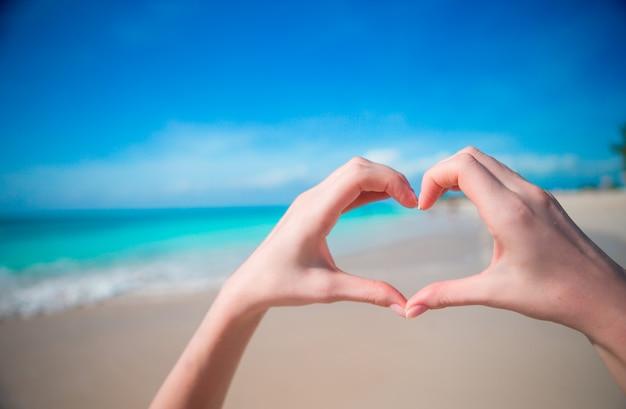 Handen in de vorm van een hart op de achtergrond van de caribische zee