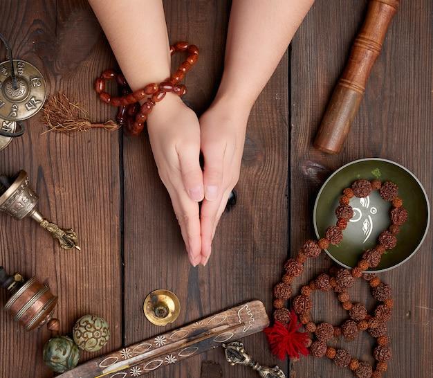 Handen in een gebed pose op een houten bruine tafel in het midden van vintage tibetaanse meditatie-instrumenten