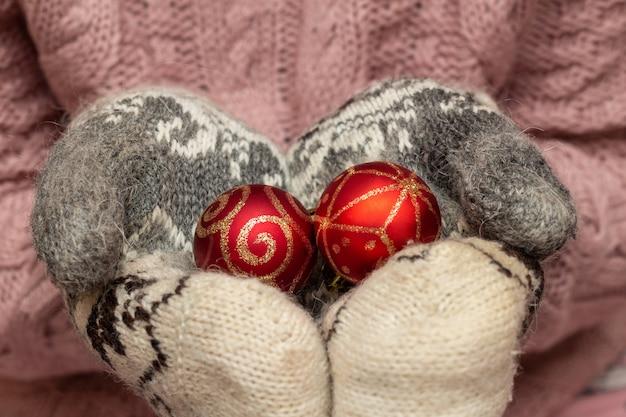 Handen in een gebreide trui wanten houden geschenk aanwezig vak. kerstvakantie voorbereiding concept.