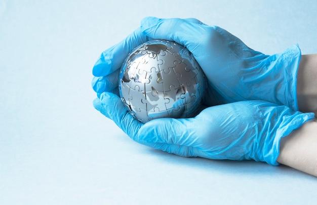 Handen in een medische blauwe handschoen houdt een kleine bol de planeet aarde, het concept van vaccinatie, bescherming, tegengaan. coronavirusbesmetting. covid-19