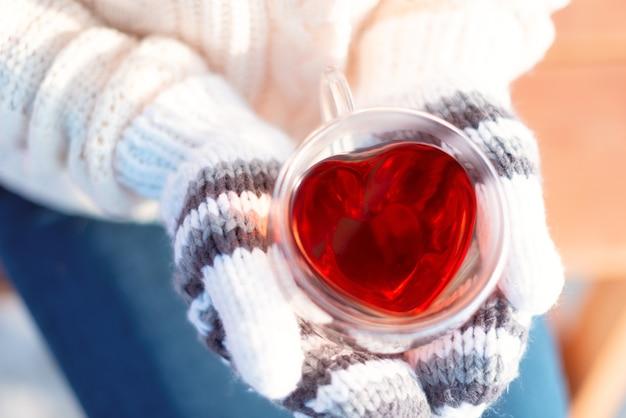 Handen in gebreide wanten houden hartvormige beker met warme drank close-up.