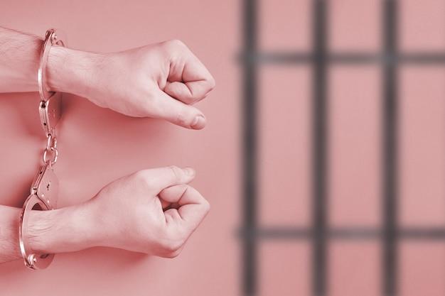 Handen in handboeien, achter de tralies. gevangenisconcept. vrijheidsberoving en arrestatie van daders. vuisten.
