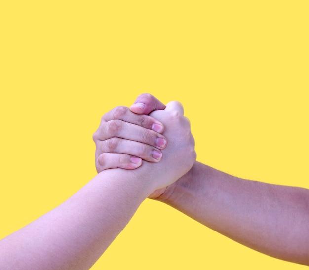 Handen in handdruk geïsoleerd op geel.