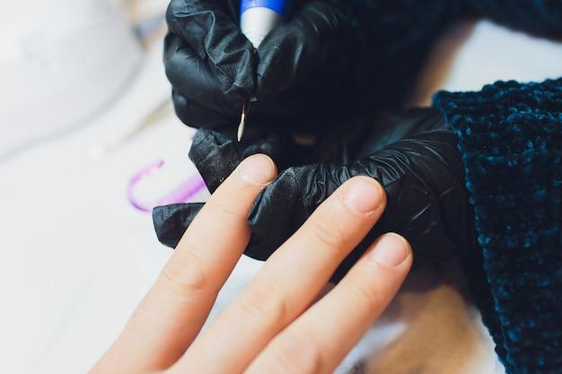 Handen in handschoenen geeft om de handnagels van de mens. schoonheidssalon manicure.