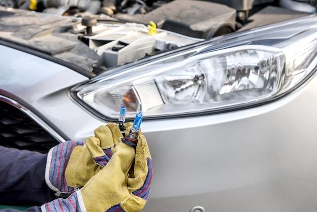 Handen in handschoenen met lampen in de buurt van autokoplampen