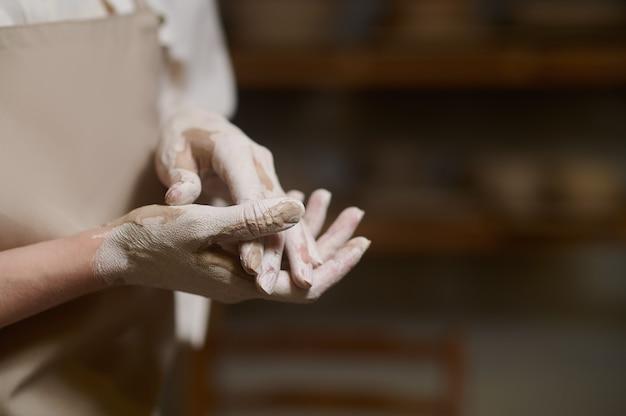 Handen in klei. close up van pottenbakkers handen in klei en met een nieuwe kom