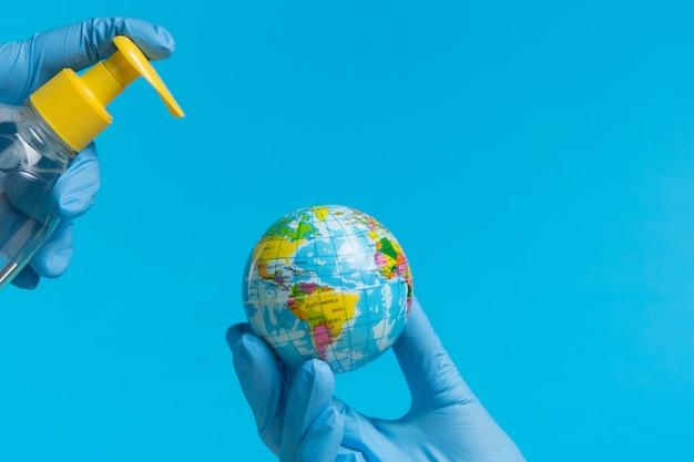 Handen in medische handschoenen desinfecteren de continenten van zuid- en noord-amerika, naar een model van de wereld, het concept van de strijd tegen coronavirus