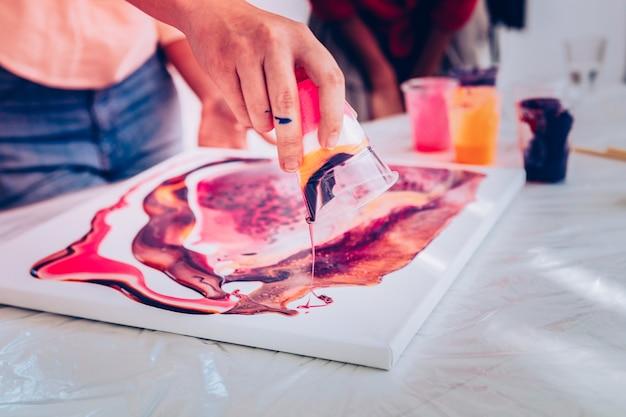 Handen in verf. sluit omhoog van jonge kunstleraar met dient verf die schildertechnieken toont