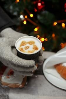 Handen in wanten houden een warme kop koffie. coffee to go in de winter