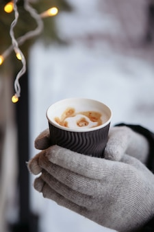 Handen in wanten houden een warme kop koffie vast. koffie voor in de winter