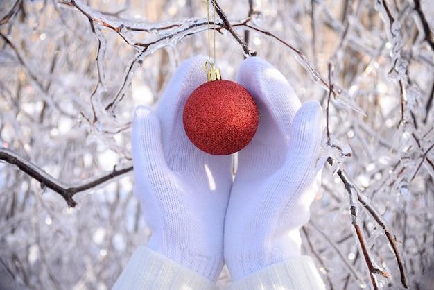 Handen in wanten met kerststuk speelgoed naast bevroren bomen bedekt met ijs