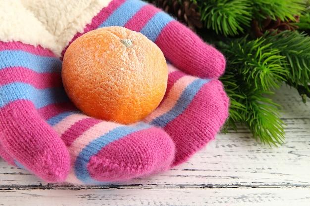 Handen in wanten met mandarijn op houten tafel