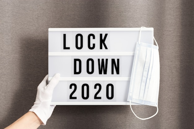 Handen in witte handschoenen houden lichtbak vast met berichtvergrendeling 2020 en chirurgisch beschermend masker.