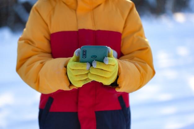 Handen in wol gele gehandschoende houdt smartphone op de achtergrond van het besneeuwde winterbos. touchscreen-handschoenen.
