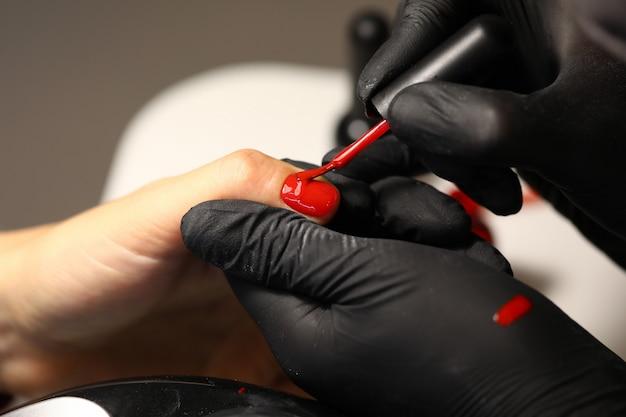Handen in zwarte handschoenen brengen rode lak aan