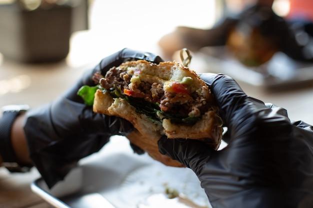 Handen in zwarte handschoenen houden een hamburgerclose-up vast
