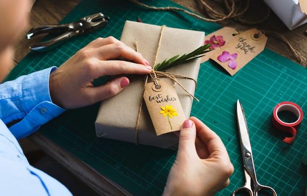 Handen inwikkeling huidige doos met bloem decoratie handwerk