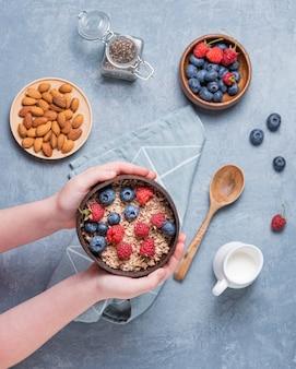 Handen kind houden kokosnoot kom met muesli, amandelnoten en bessen op blauwe achtergrond. energie en veganistisch ontbijt. bovenaanzicht