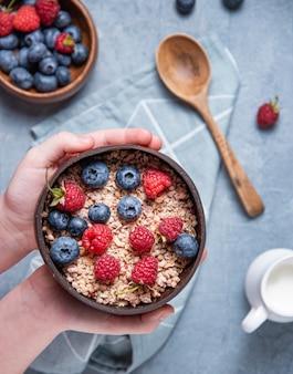 Handen kind houden kokosnoot kom met muesli en bessen op blauwe achtergrond. energie en veganistisch ontbijt. bovenaanzicht
