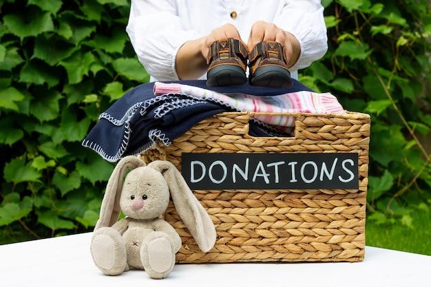 Handen kinderschoenen aanbrengend een doos voor donaties