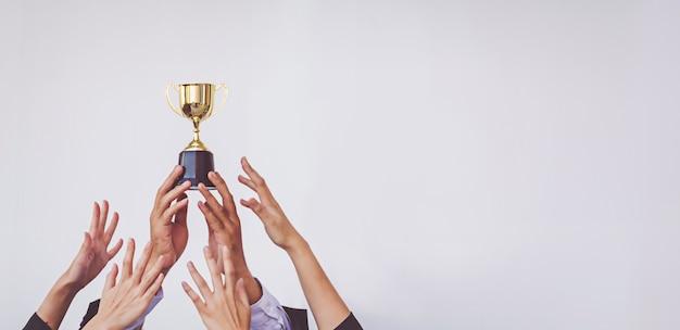 Handen klauteren voor de gouden trofee cup, concept bedrijf