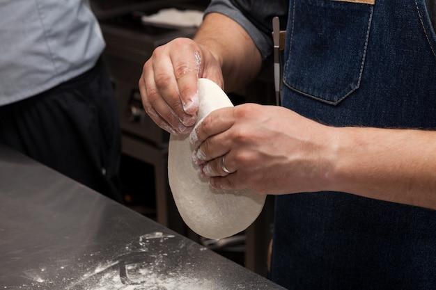 Handen kneden deeg voor pizza of focaccia