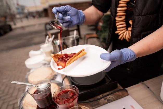 Handen kookt in blauwe handschoenen, houdt een bord pannenkoeken vast en legt een vulling op. pannenkoekenweek