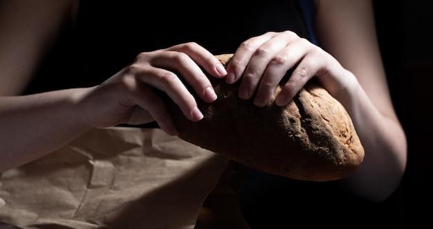 Handen kraken heerlijk vers brood uit een papieren zak. donkere achtergrond.
