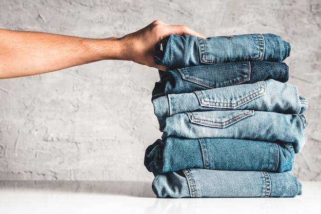 Handen, leg de stapel blauwe spijkerbroek op grijs.