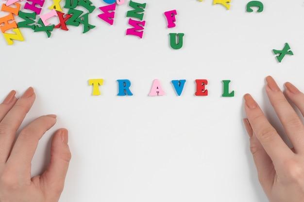 Handen leggen het woord reizen uit gekleurde letters op