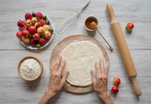 Handen maken deeg appeltaart of goji-bes. appeltaart voor de vakantie.