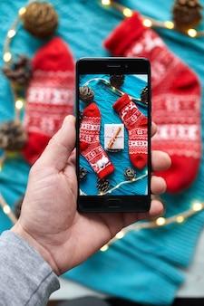 Handen maken een foto van de compositie van kerstmis en nieuwjaar met rode sokken en een geschenkdoos van ambachtelijk papier