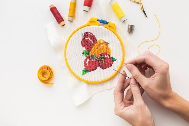 Handen maken een ontwerp met naald en naaigaren