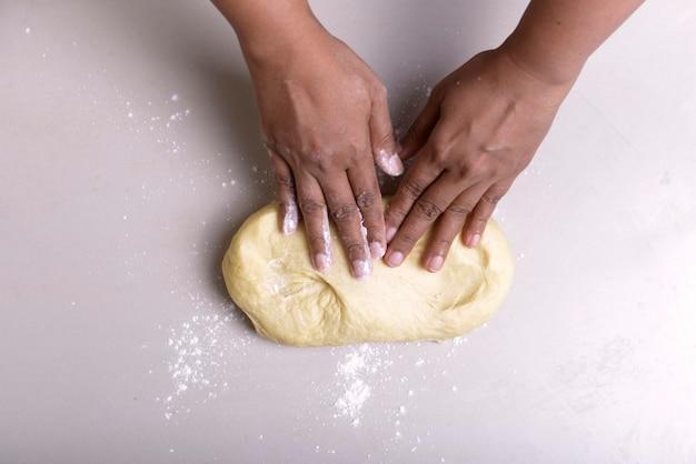 Handen maken van deeg op tafel